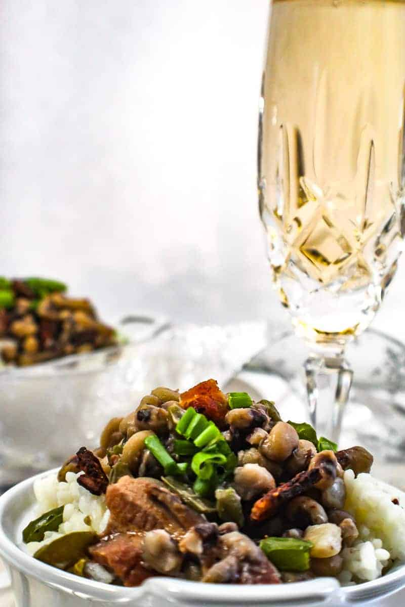 Good Luck Black Eyed Peas in bowl next to a glass of champagne