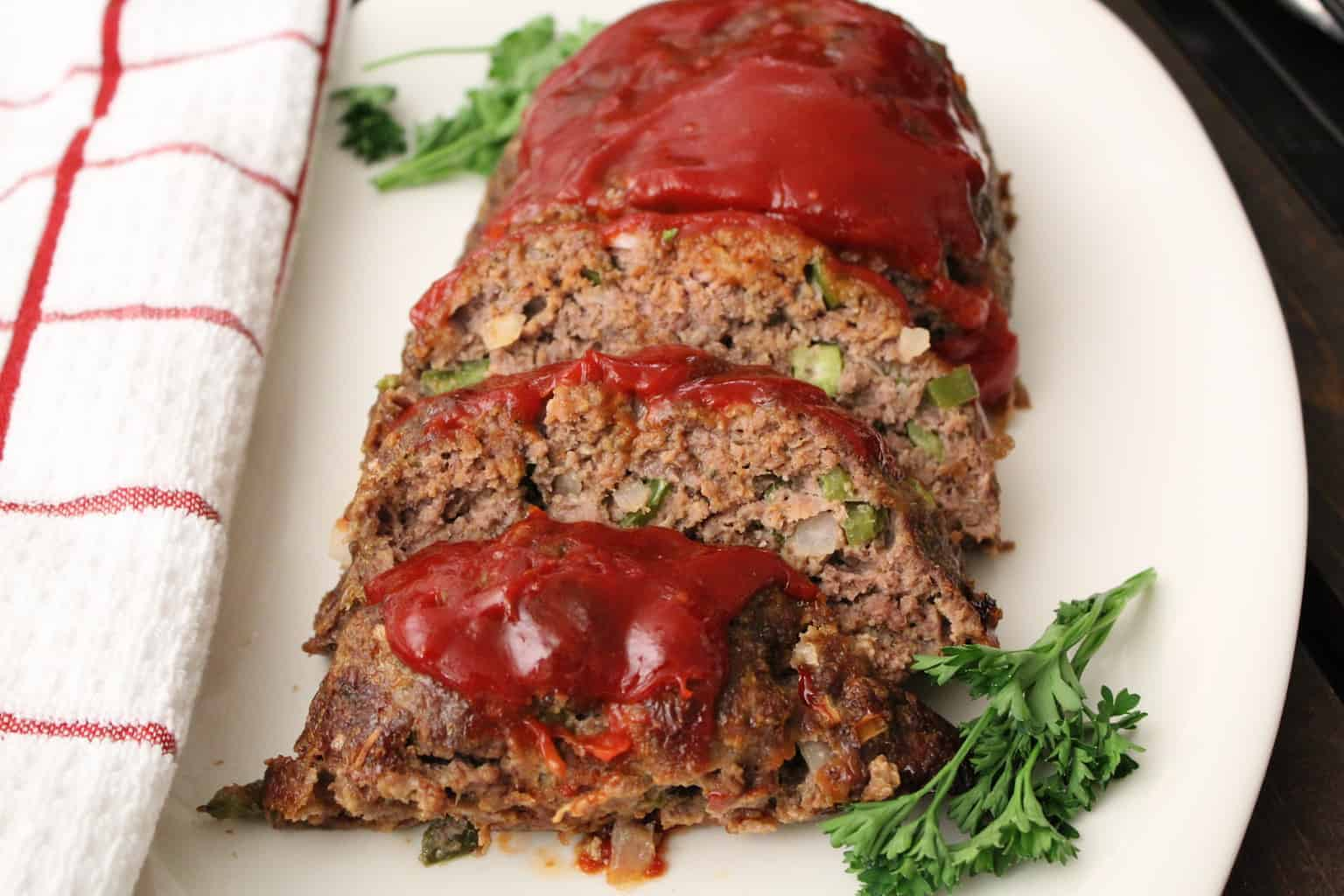 Classic Meatloaf sliced on white platter topped with tomato sauce