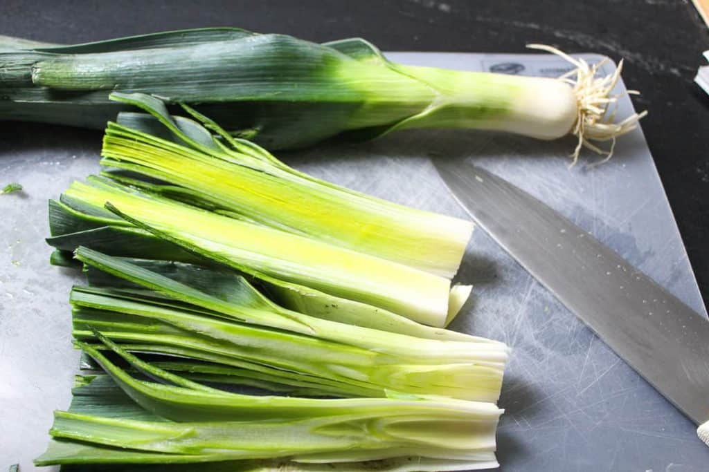 Leeks cut lengthwise on a cutting board