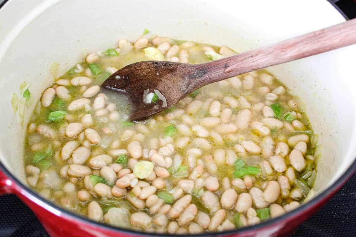 White beans, broth and vegetables in stockpot with wooden spoon