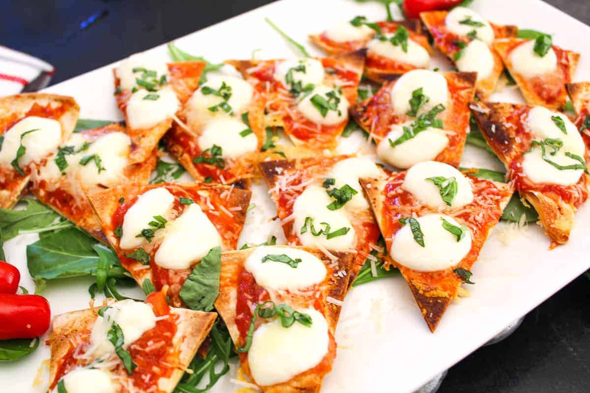 Margherita Nachos on white serving platter with fresh basil