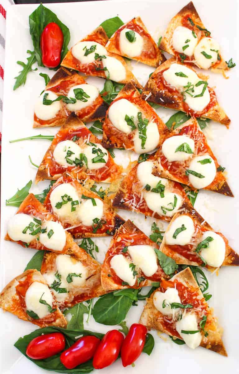 Margherita Nachos cut into triangles on a white serving platter