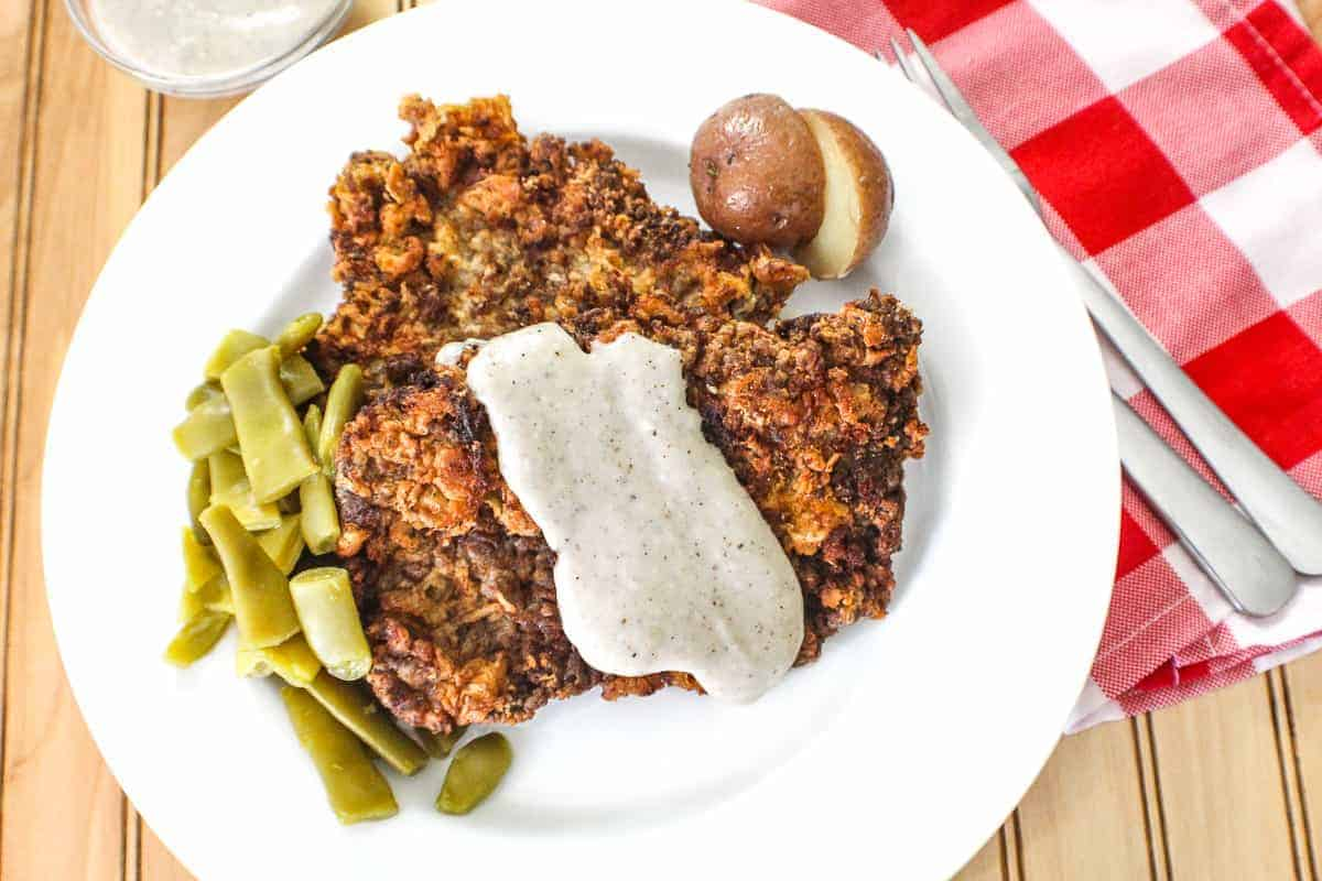 Chicken fried steak with cream gravy, potatoes and green beans on white plate