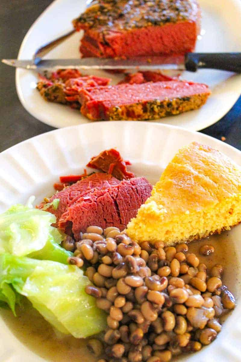 Corned beef, cabbage, blackeyed peas and cornbread on white plate
