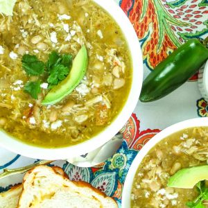 Green chile soup garnished with avocado.