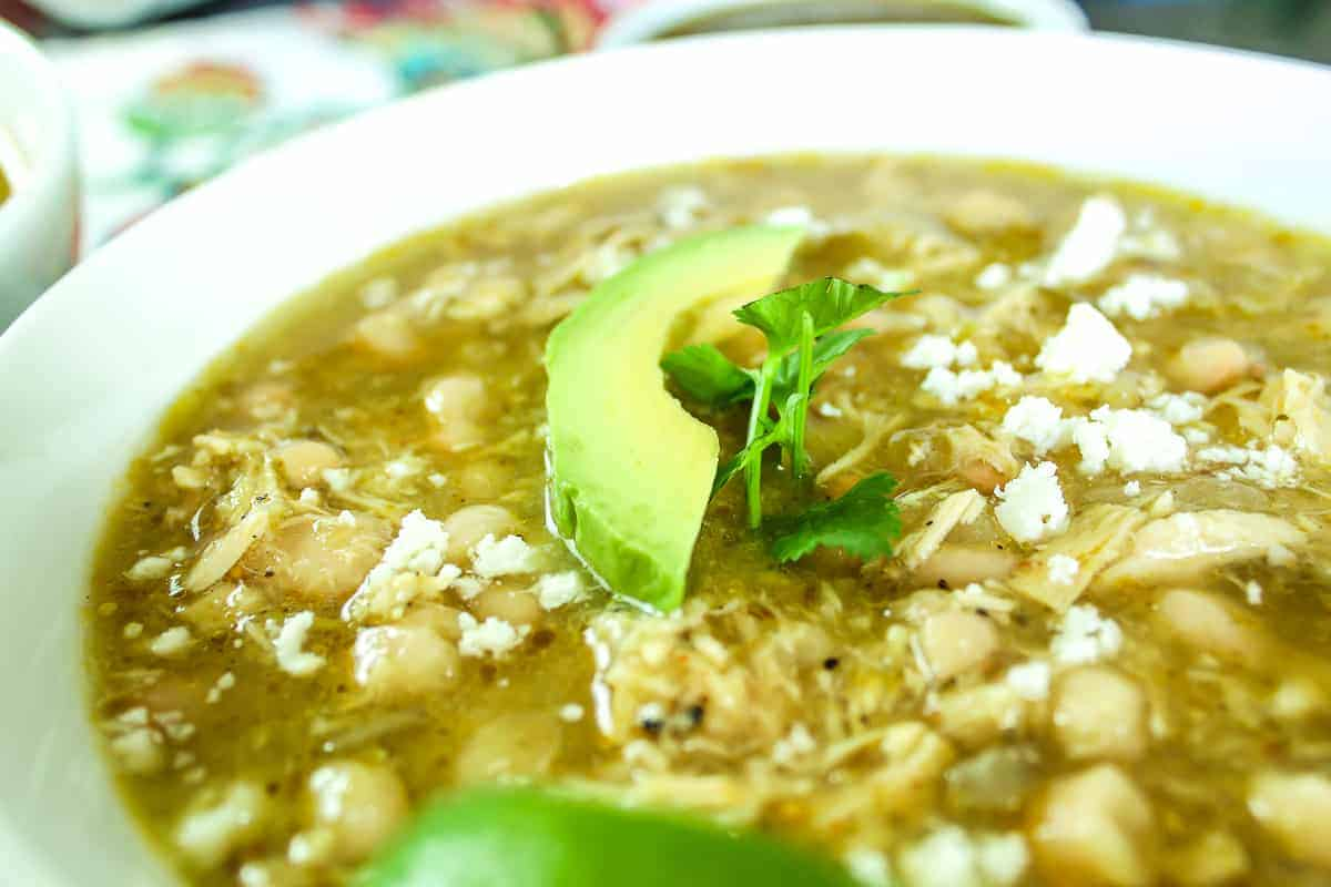 Close up image of soup garnished with avocado and cheese
