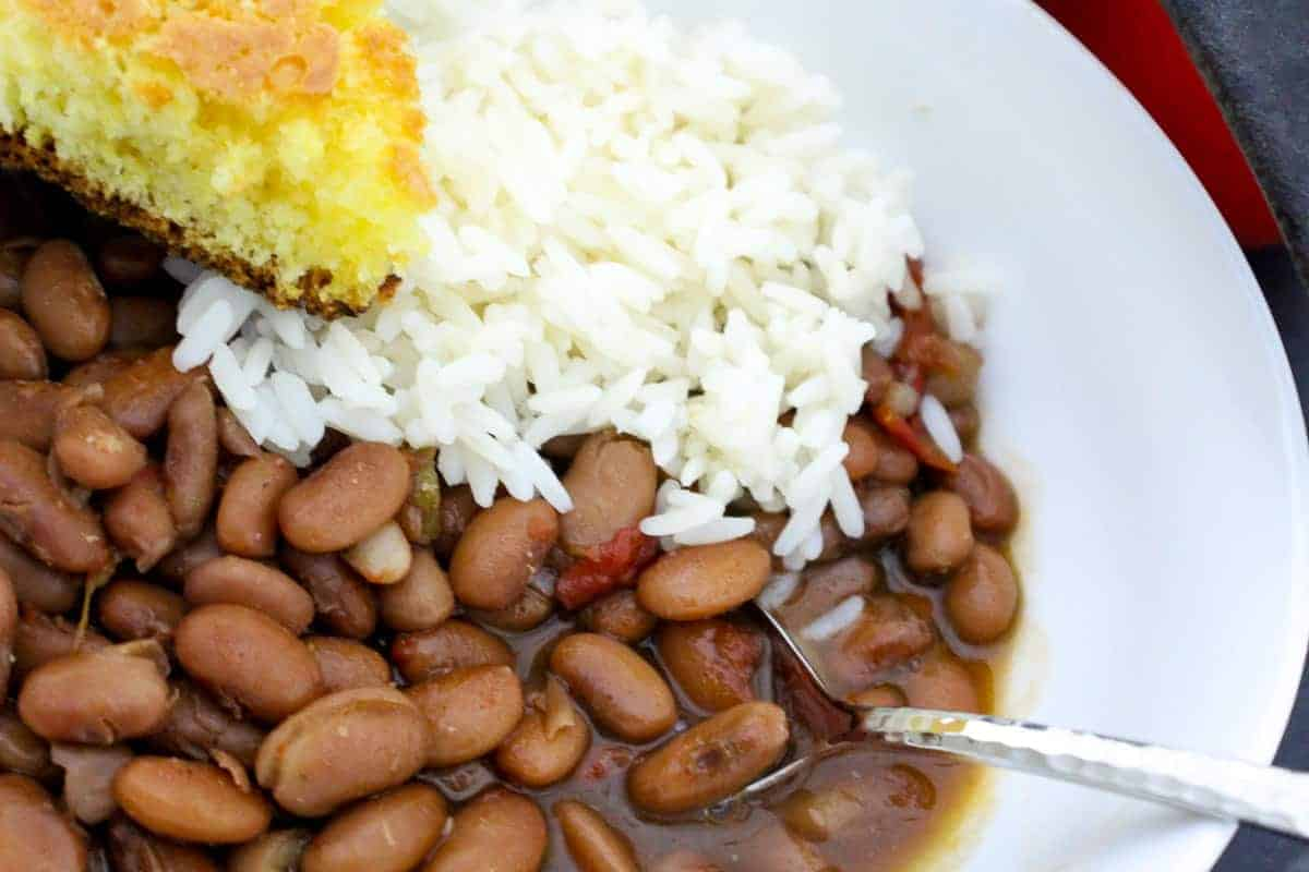 White rice and pinto beans with a slice of cornbread in a white bowl