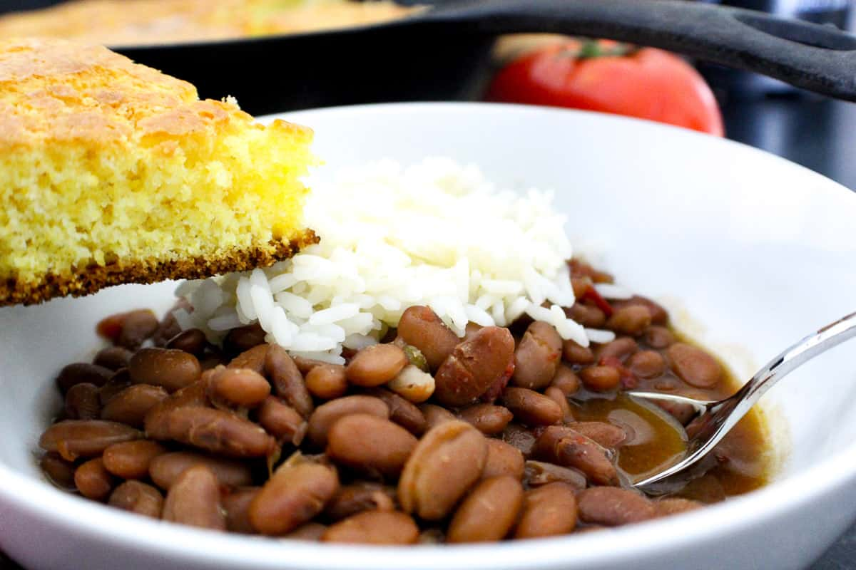 Pinto beans and rice in a bowl with a side of cornbread