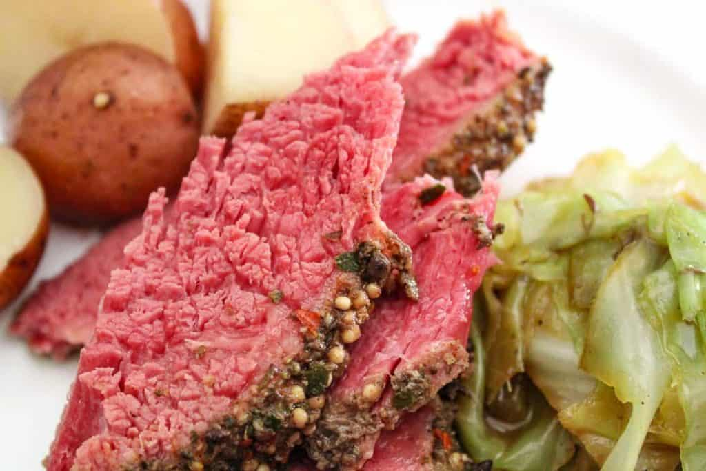 Close up image of cooked corned beef and cabbage with a potato in the background