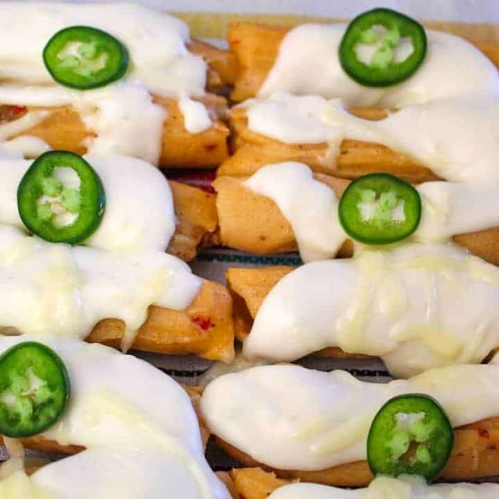 Tamales in baking dish with sour cream sauce and sliced jalapeno on top