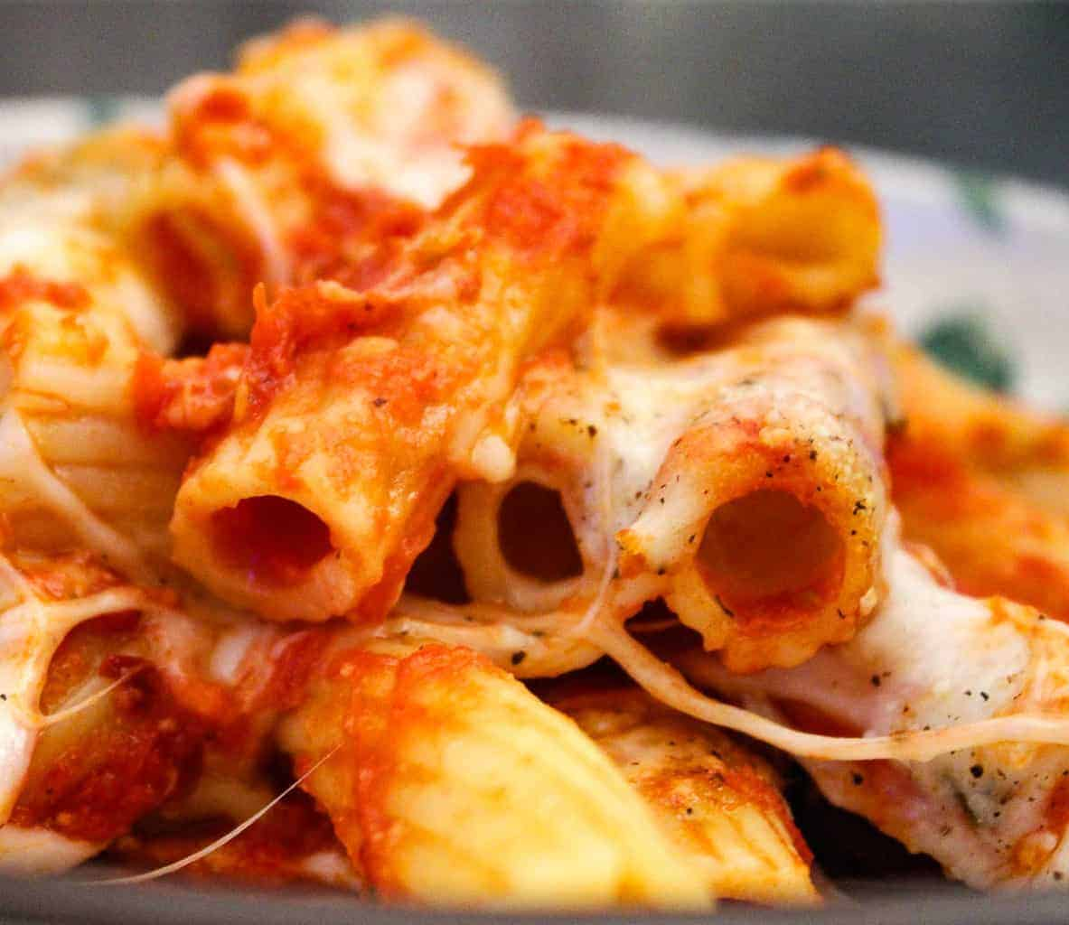Close up of baked rigatoni with tomato sauce and cheese
