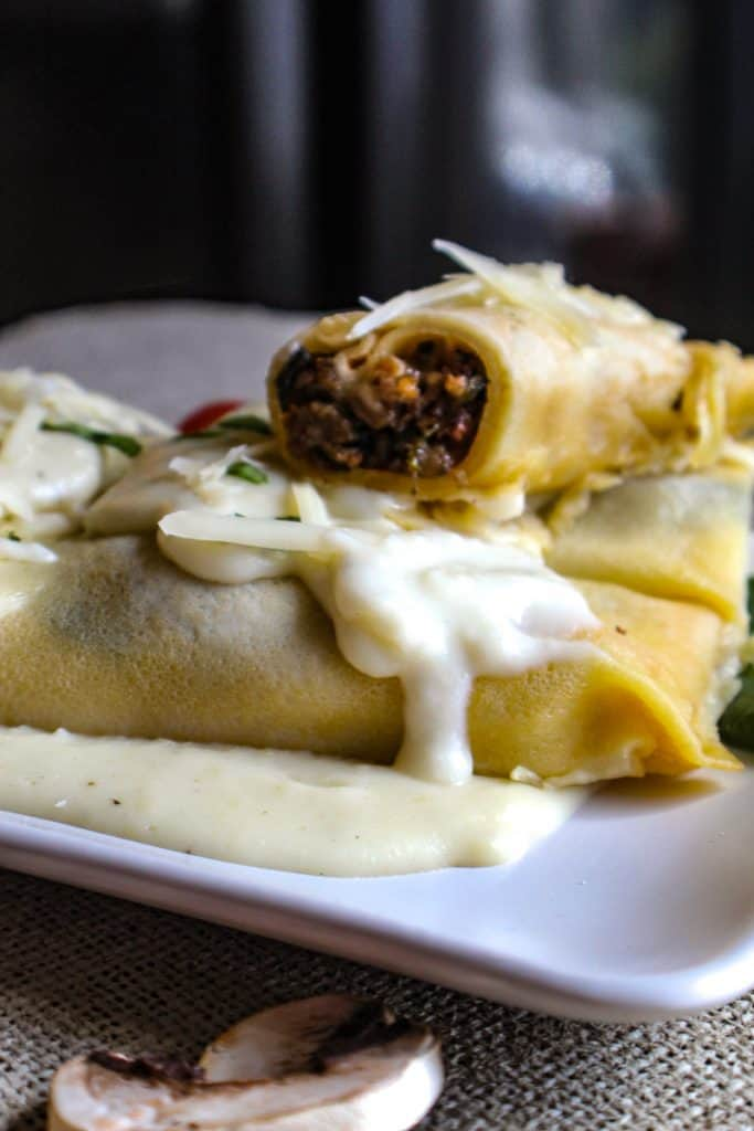 Close up of sausage crepe cut in half topped with Gruyere sauce