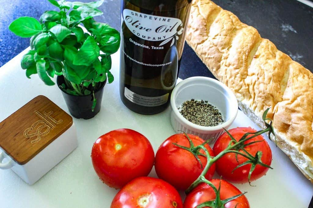 Tomatoes, basil, basil, salt, olive oil and bread on white cutting board