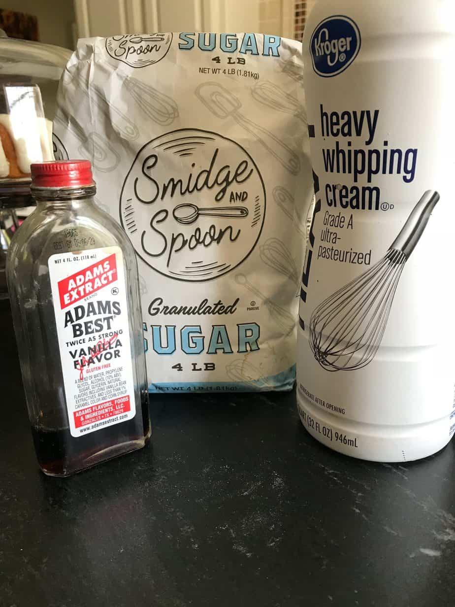 Vanilla extract, sugar and heavy cream on countertop