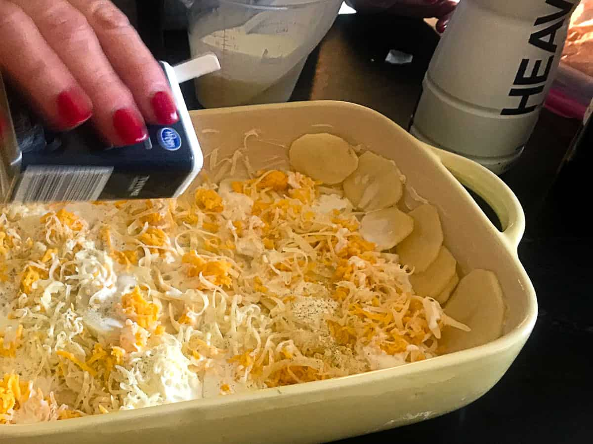 A sprinkling of thyme being added to the cheese layered potatoes in baking dish