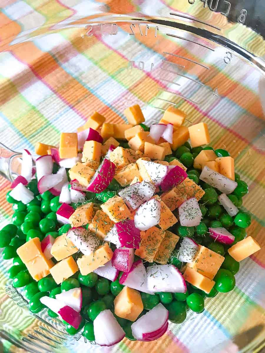 Clear bowl with red onion, cubed cheddar and green peas