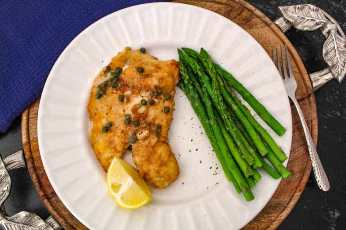 Lemon chicken piccata with asparagus on white plate