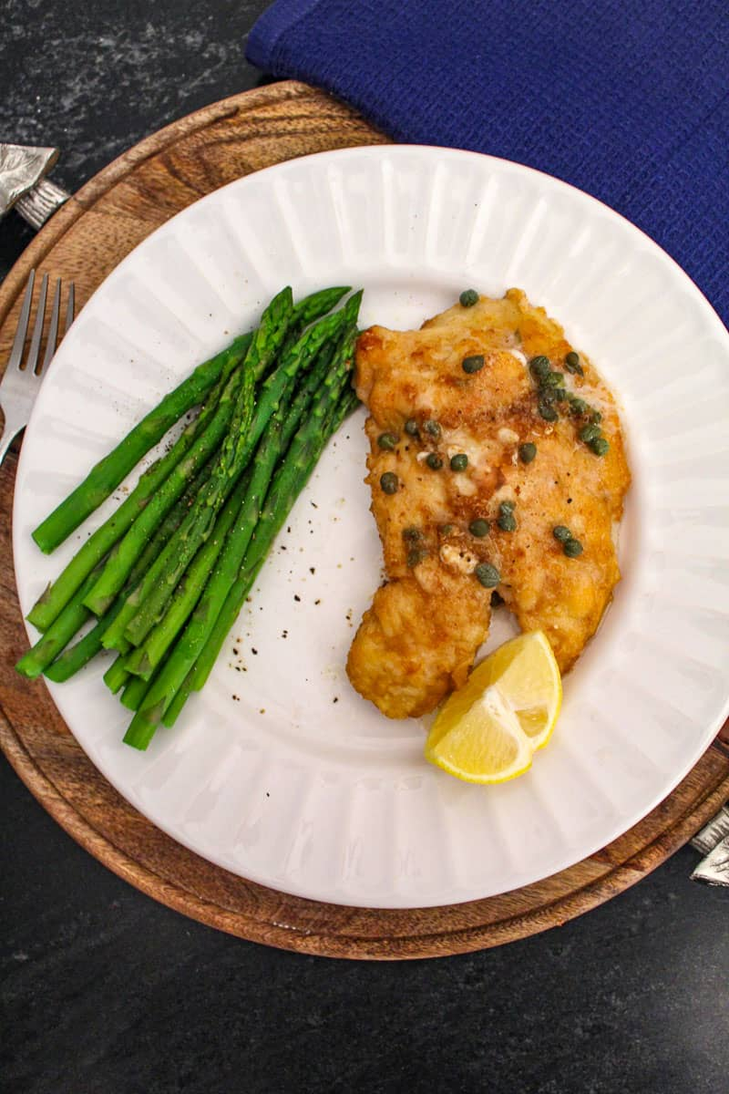 Chicken Piccata and asparagus on white dinner plate.