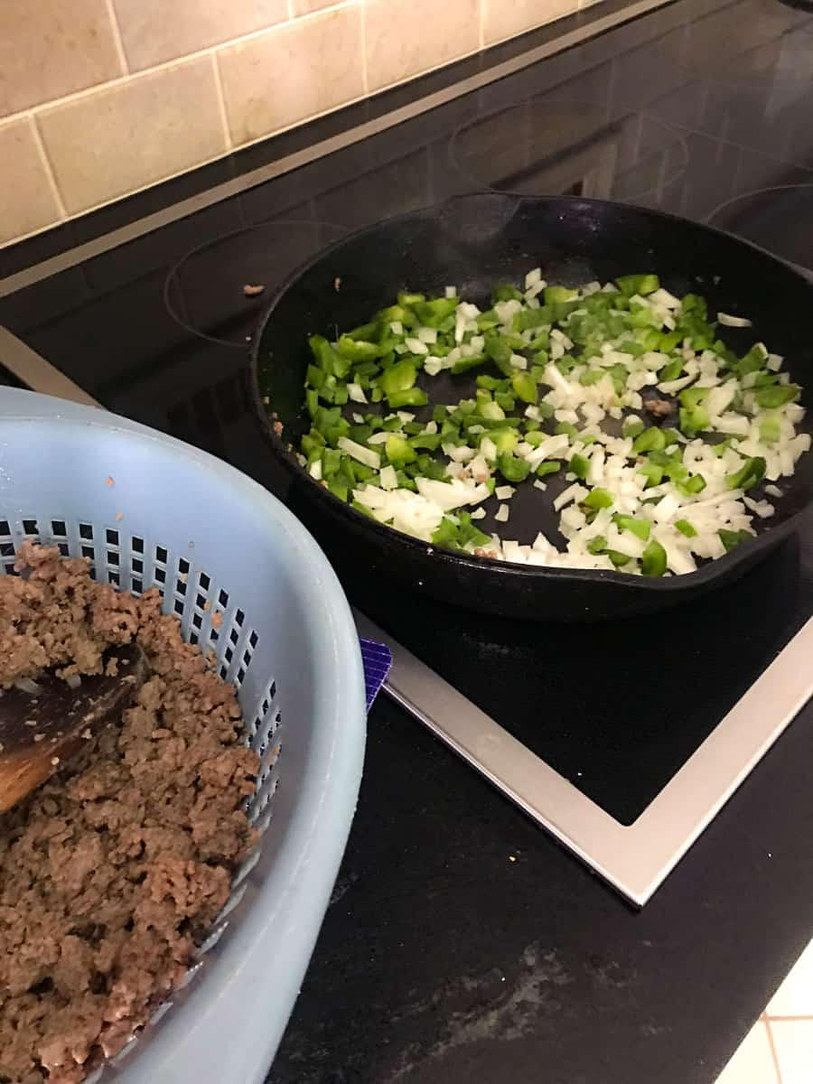 Browned meat in colander next to cast iron skillet with bell pepper and onion