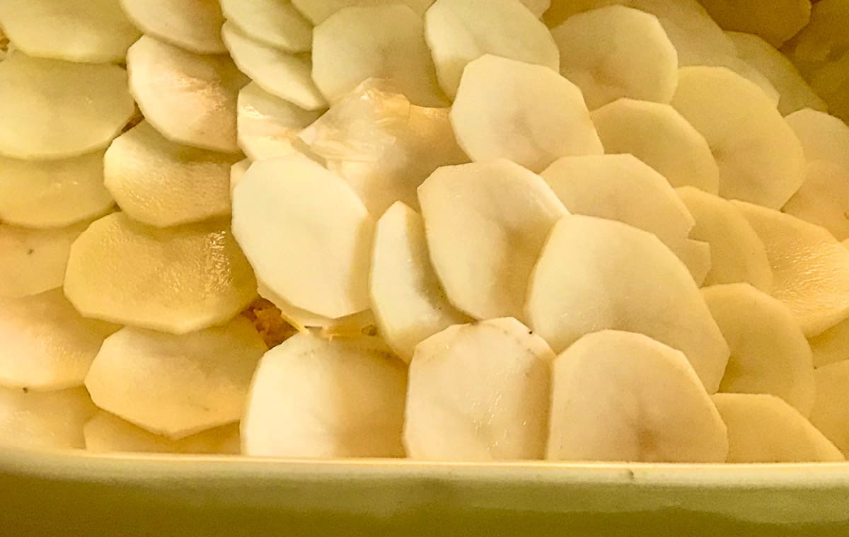 Layer of thin sliced potatoes in pan