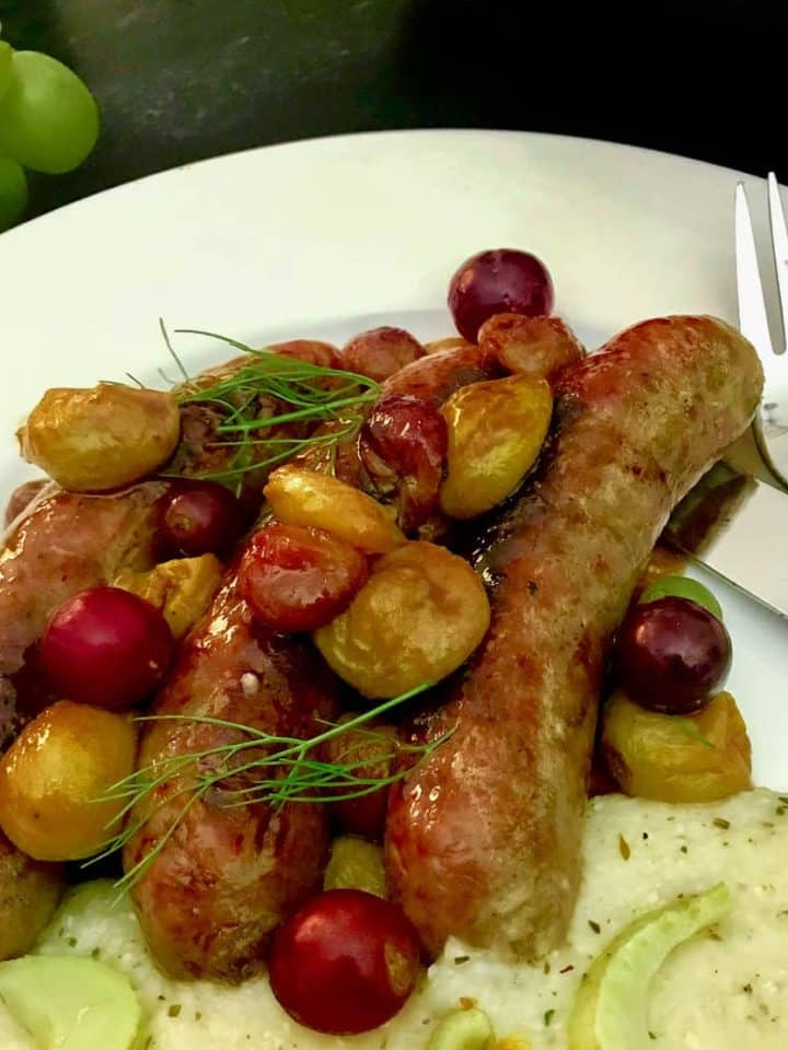 Italian sausage links and roasted grapes on white plate