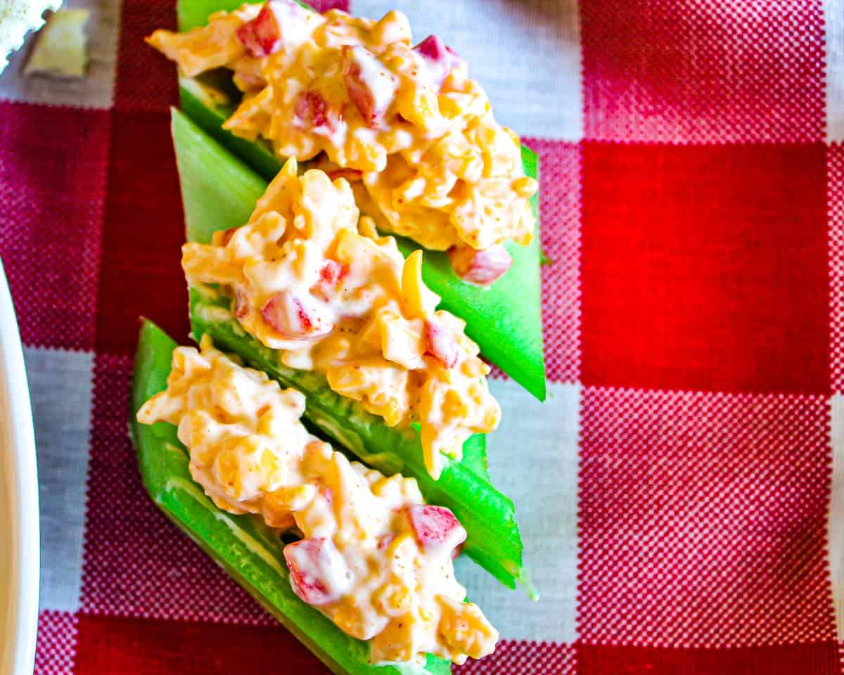 Three short celery stalks stuffed with pimento cheese on red checkered tablecloth
