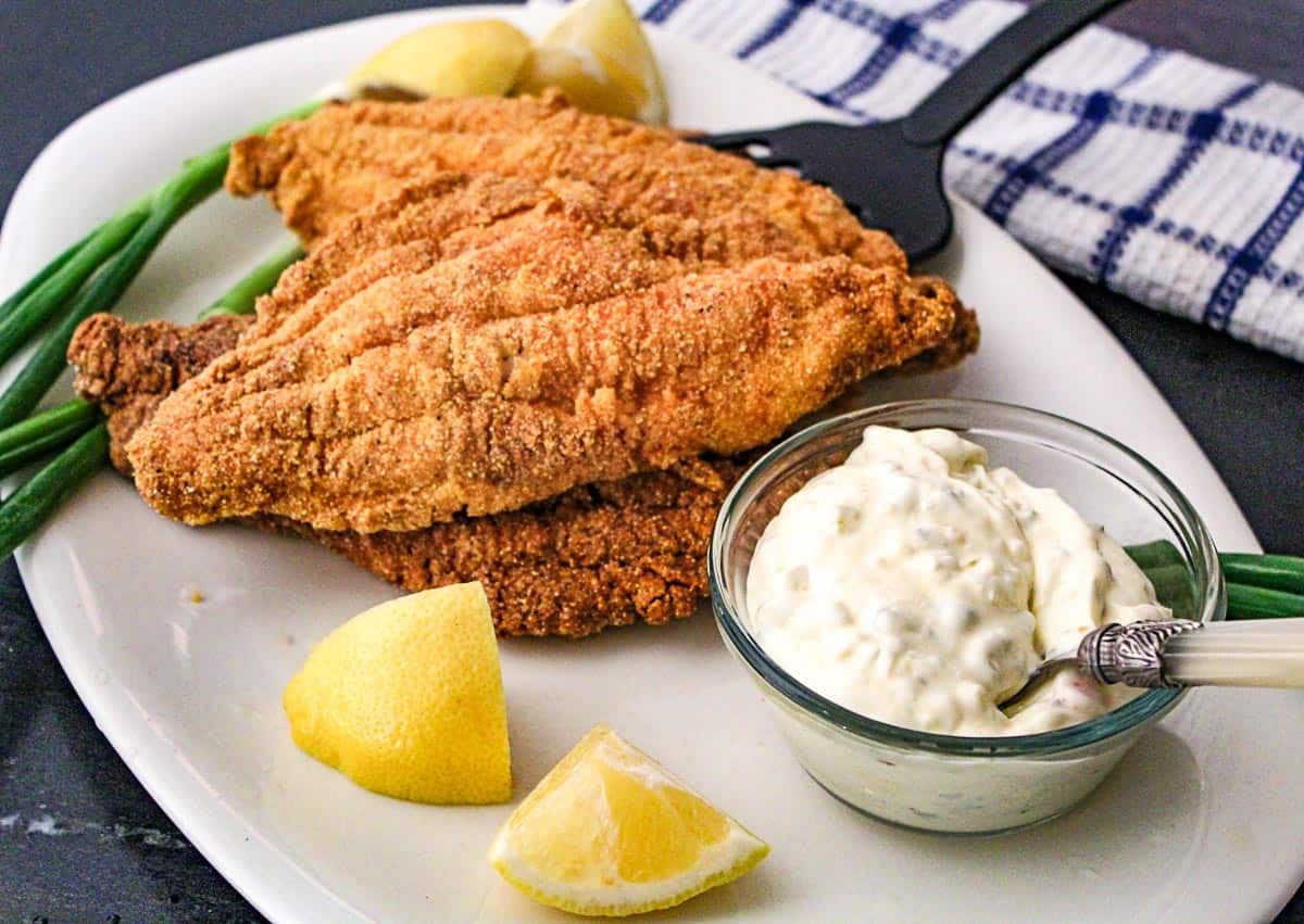 Fried catfish with lemon and tartar sauce on a white platter