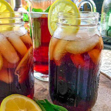 Mason jars full of iced tea with lemon on patio table