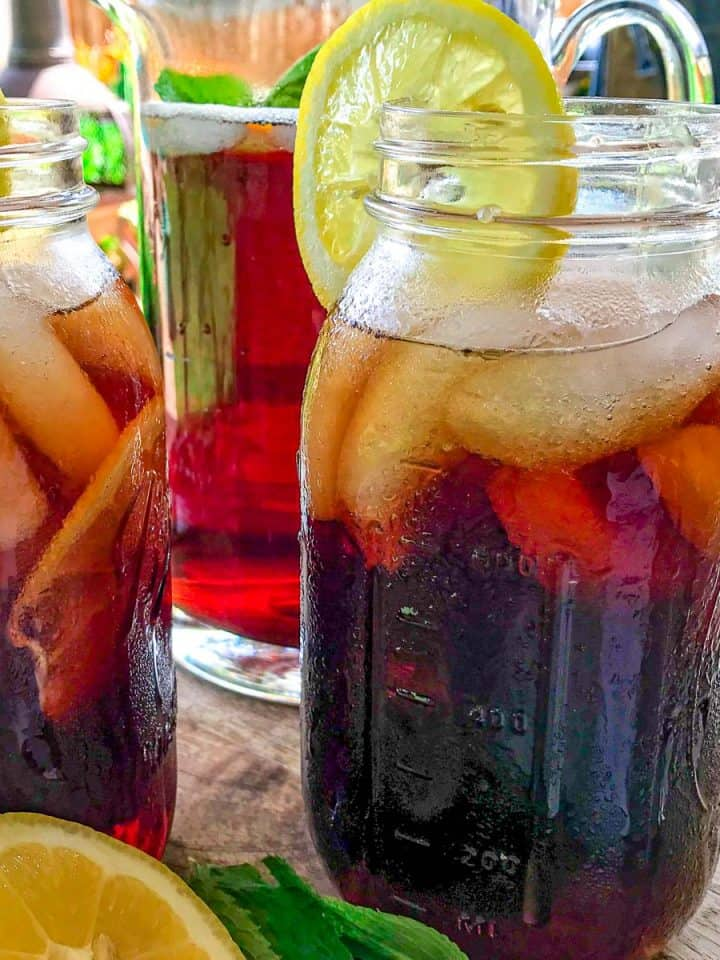 Mason jars full of iced tea with lemon on patio table