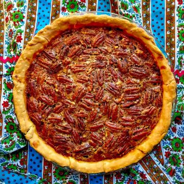 Whole pecan pie on colorful tablecloth