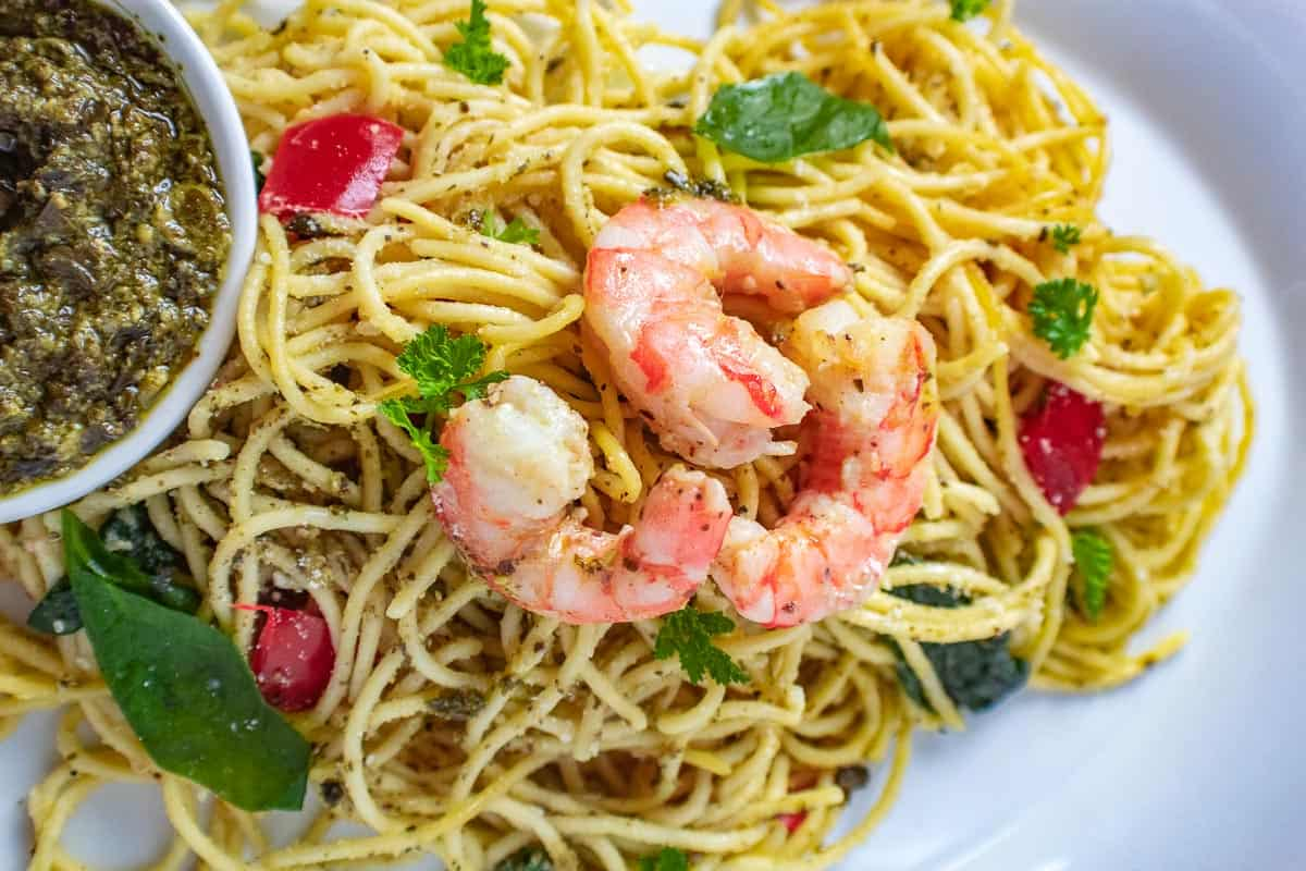 Shrimp on pasta with a side of pesto sauce