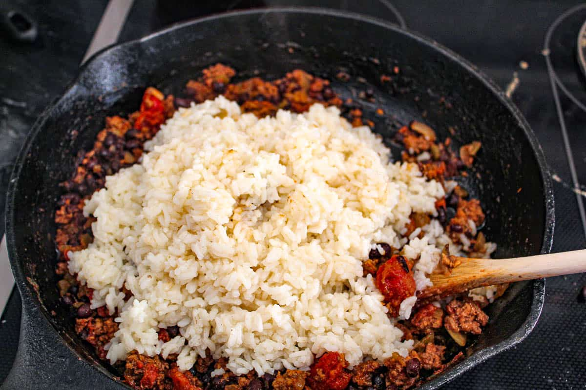 Prepared rice over ground beef in cast iron skillet