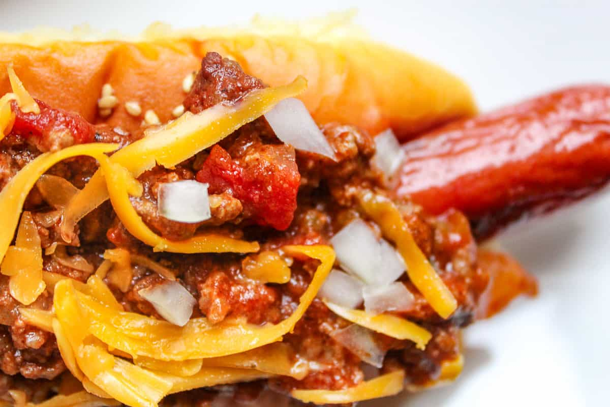 Chili dog garnished with onion and cheese