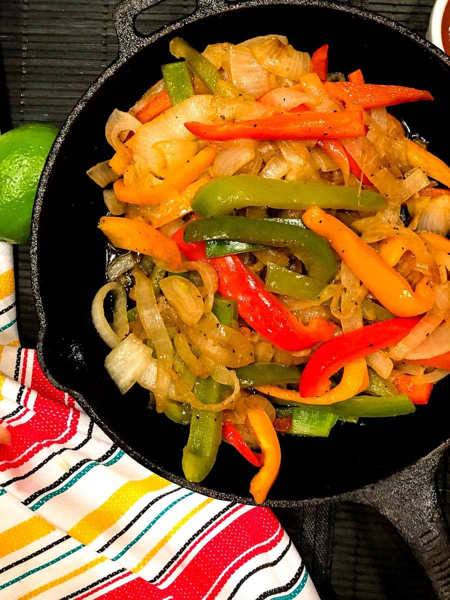 Sliced red, yellow and green bell peppers and onions in cast iron skillet