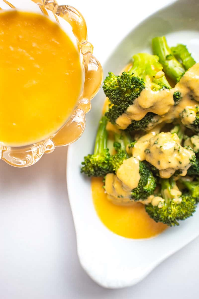 White bowl of broccoli with cheese sauce on it; side of cheese sauce