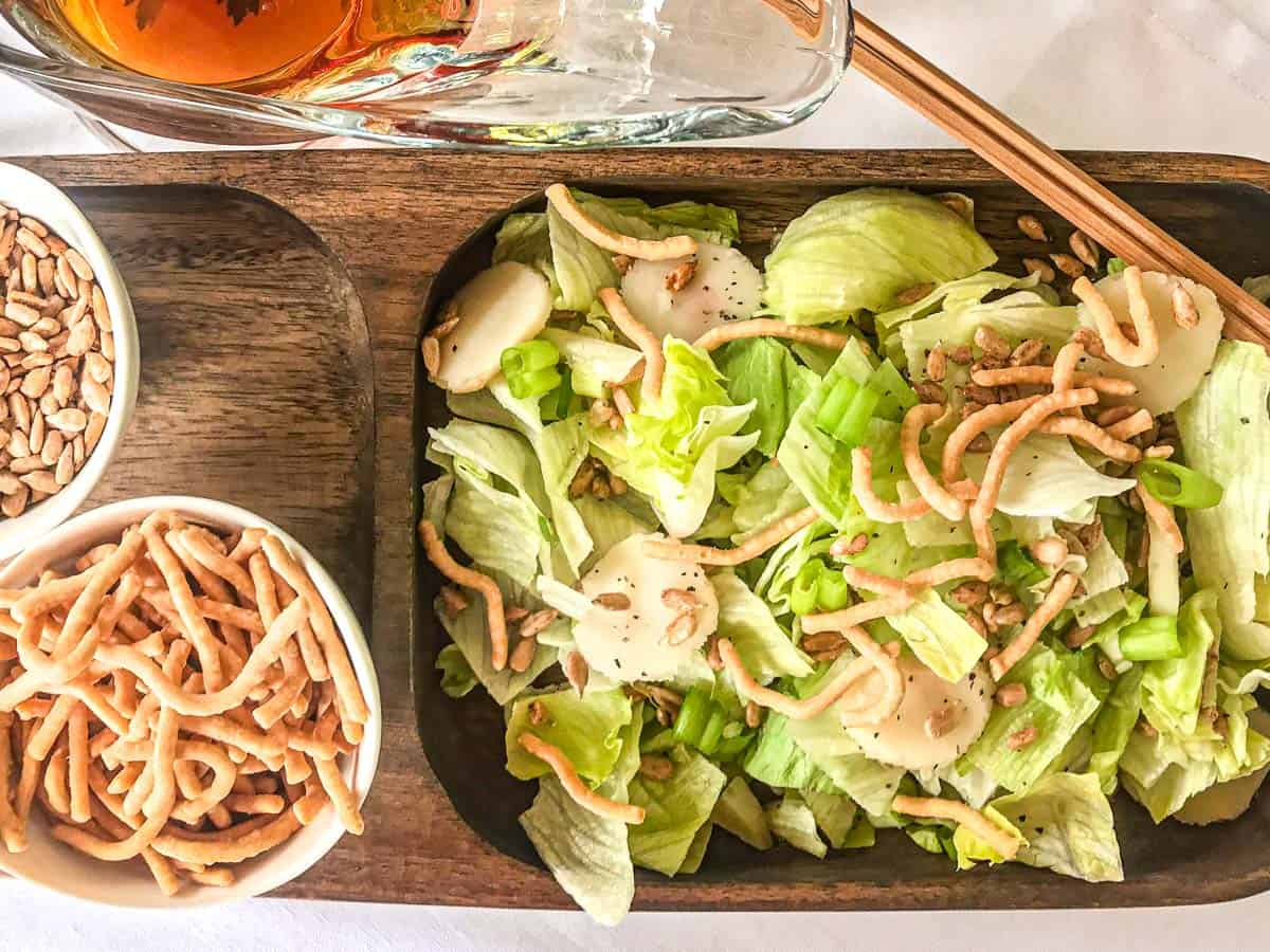 Salad on wooden plate with a side of noodles and sunflower seeds