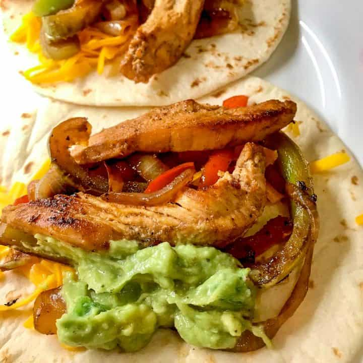 Tex Mex fajitas open faced on a white plate