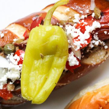 Hot dog in pretzel bun garnished with capers, feta cheese and a pepperocini