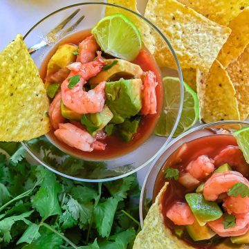 Shrimp and avocado in tomato broth garnished with lime wedge and tortilla chip