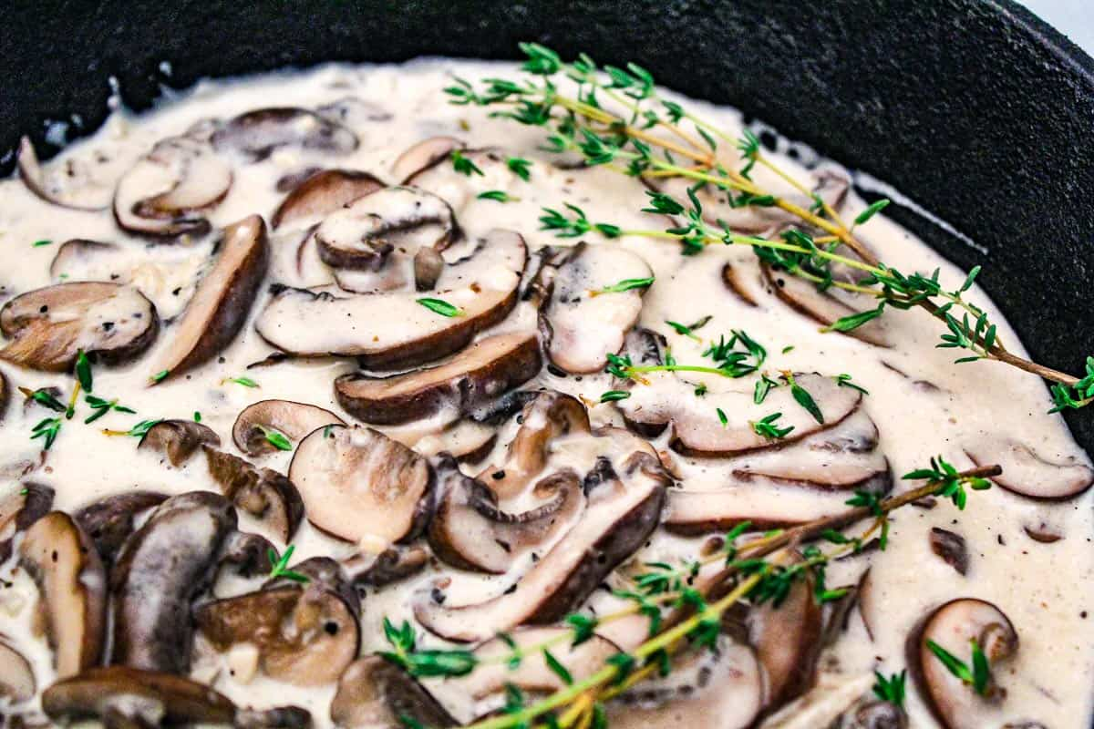 Mushroom Cream Sauce garnished with sprigs of thyme in a black skillet