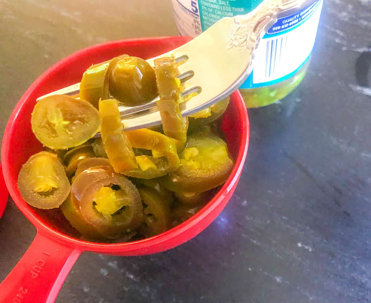Jalapenos in a measuring cup with a fork
