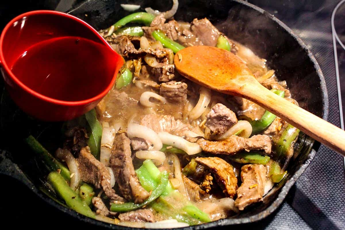 Sliced beef, onions and peppers and broth in pan
