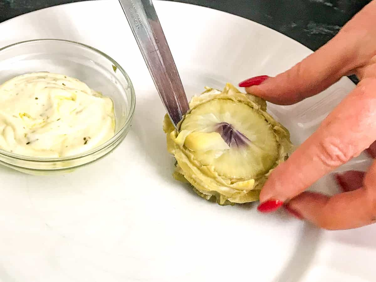 Knife being inserted into artichoke heart on white plate