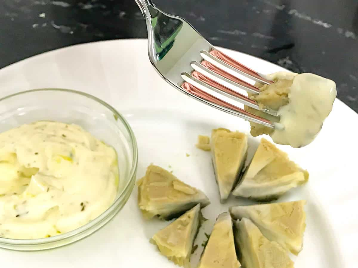 A bite of artichoke heart on a fork dipped in mayonnaise sauce
