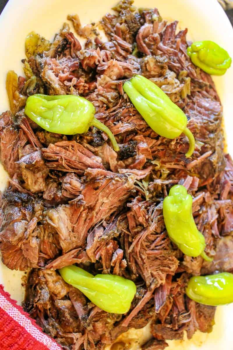 Shredded Mississippi Pot roast with Pepperoncini peppers on white plate