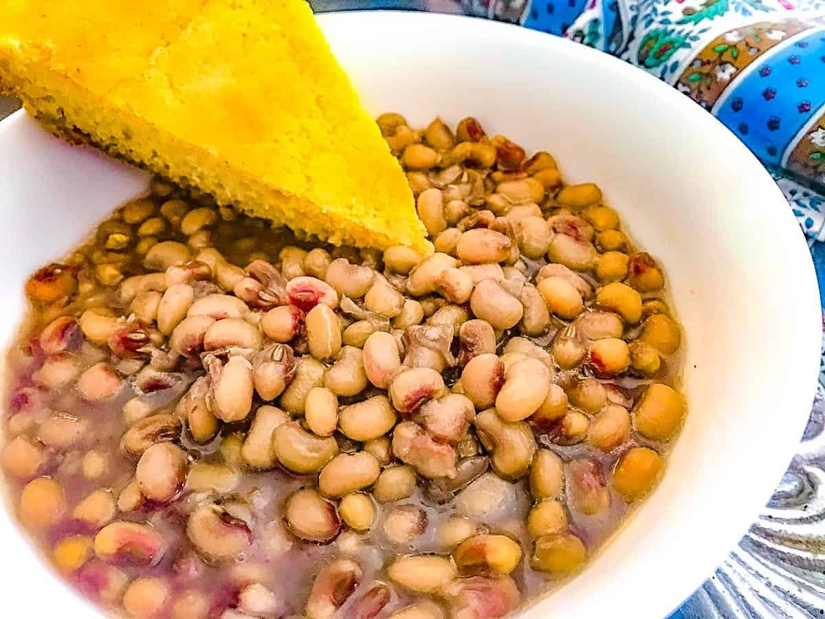 Cooked purple hull peas in a white bowl with a slice of cornbread