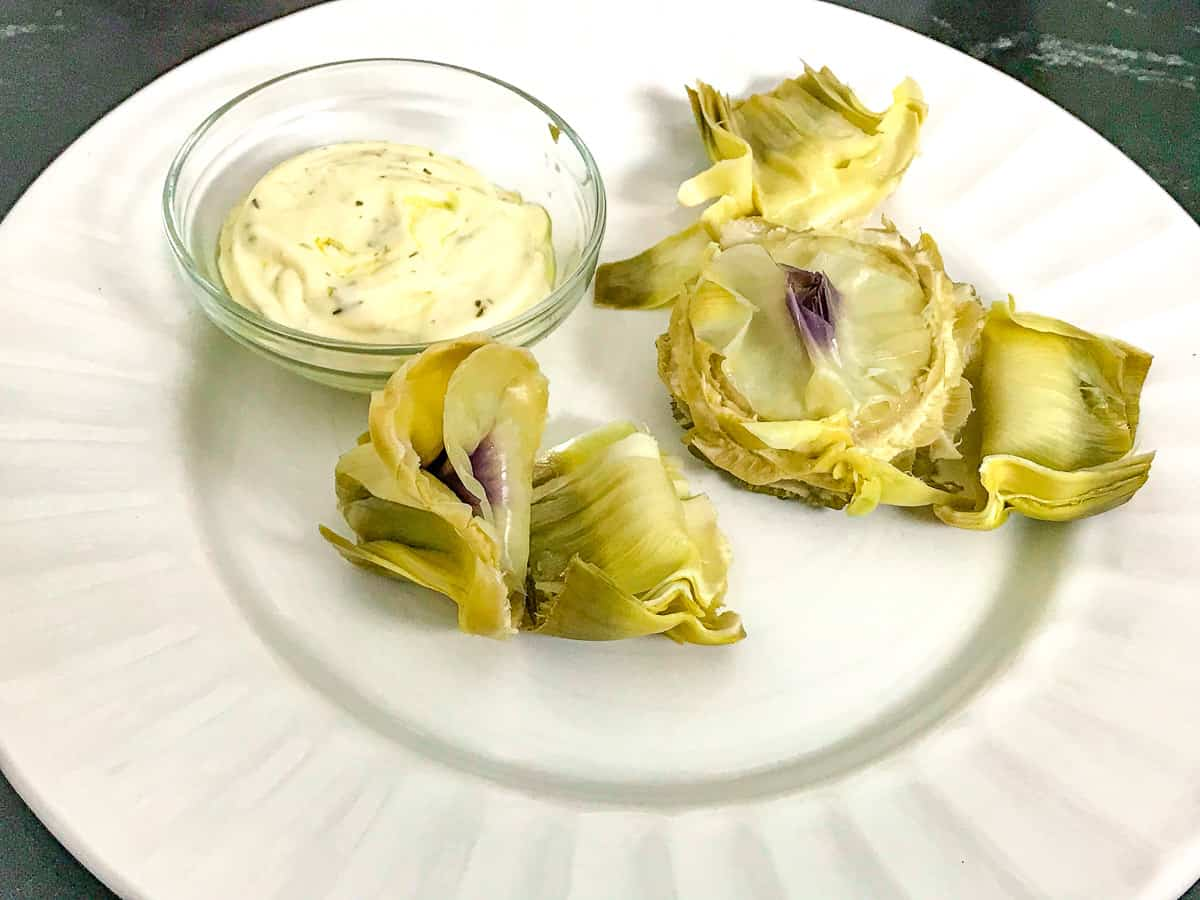 Artichoke heart with a side of mayonnaise sauce on white plate