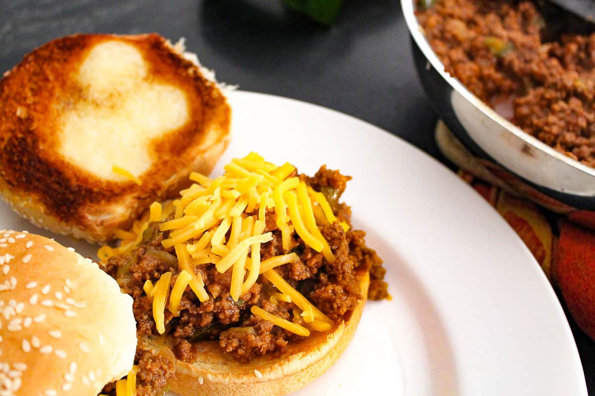 open faced sloppy joe topped with shredded cheddar on white plate