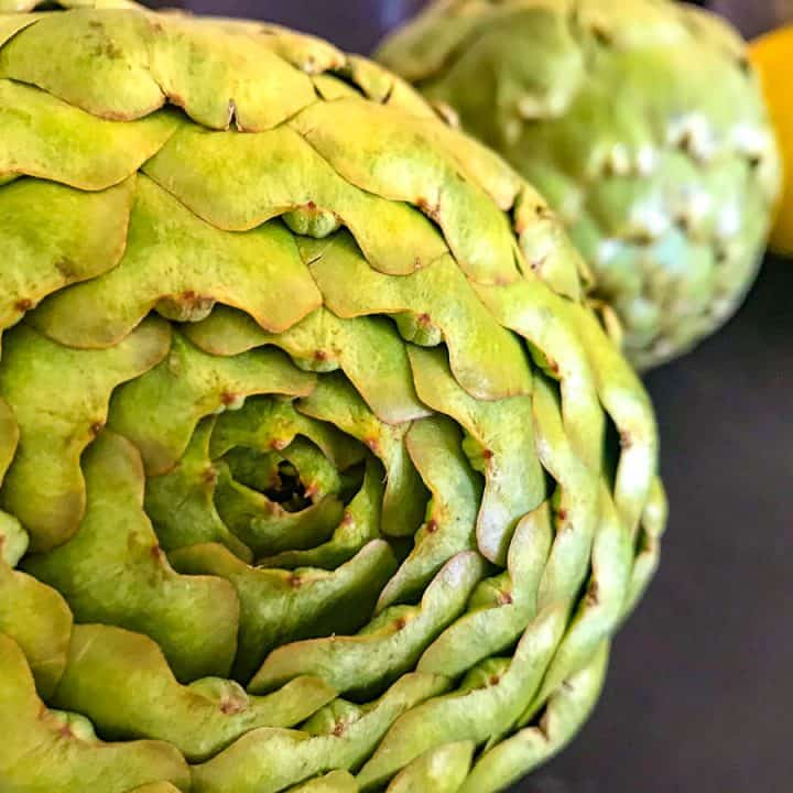 Whole artichoke on black counter