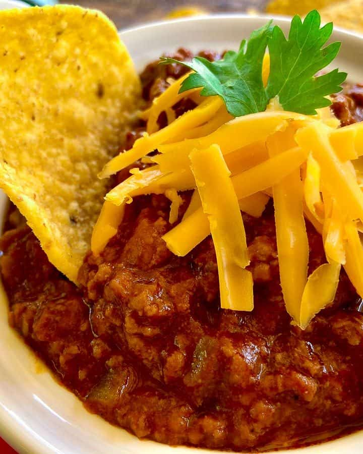 Chili in white bowl with tortilla chip and shredded cheese